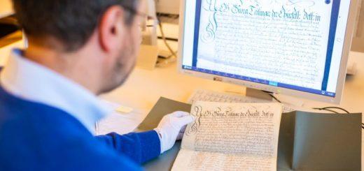 Dr. Roland Götz mit dem Original und der digitalen Ansicht eines Dokuments