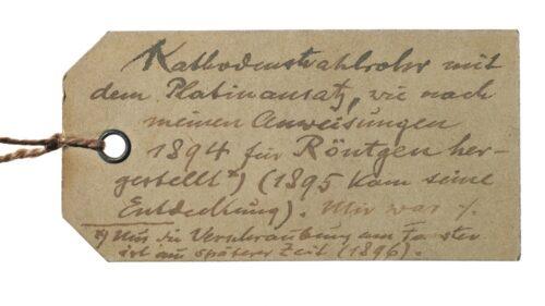 """Beschriftung für das Kathodenstrahlrohr (DMA, CD 66151 und CD 66152). Lenard vermutete, Röntgen habe bei der Entdeckung der Röntgenstrahlen mit einer Röhre gearbeitet, die nach Lenards Angaben gefertigt worden war. Diese Ansichten hielt er auf dem Beizettel fest: """"Kathodenstrahlrohr mit dem Plantinansatz, wie nach meinen Anweisungen 1894 für Röntgen hergestellt (1895 kam seine Entdeckung)."""" Blogparade #Deutungskämpfe"""