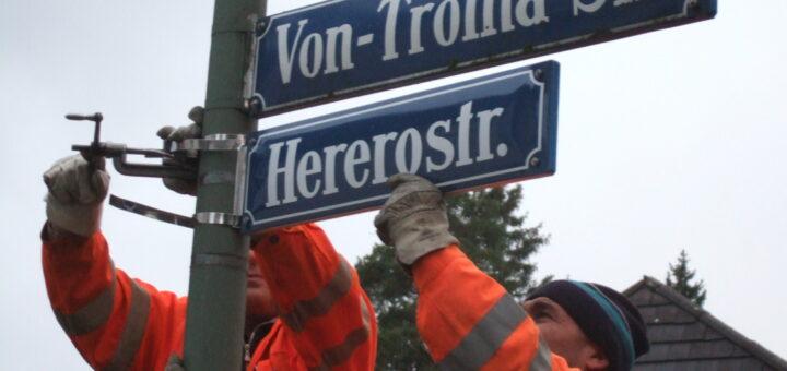 """Zwei Arbeiter montieren das neue Straßenschild """"Hererostraße""""; Straßenumbenennung der Von-Trotha-Straße in Hererostraße in München, 2007 (Henning Hintze, Sammlung [muc] münchen postkolonial) Deutungskämpfe"""